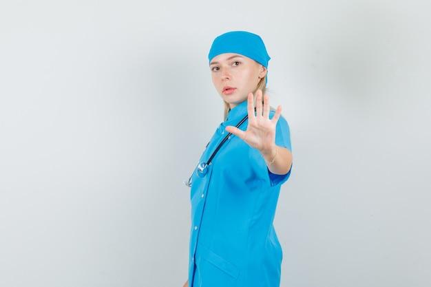 Женщина-врач в синей форме показывает жест отказа рукой и выглядит серьезно. Бесплатные Фотографии