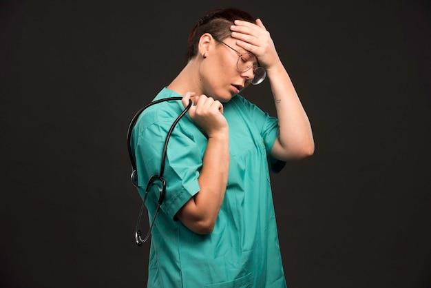 聴診器を持って疲れているように見える緑色の制服を着た女性医師。 無料写真