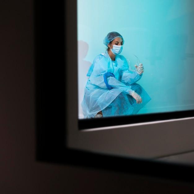Женщина-врач в пандемическом оборудовании, сидя в больнице устала Бесплатные Фотографии