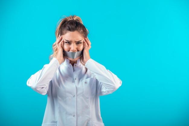 彼女の口と耳を覆う白い制服を着た女医。 無料写真