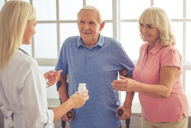 Female doctor is talking to old couple and holding a bottle Premium Photo