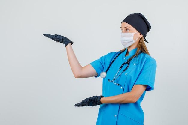 Medico femminile che tiene i palmi aperti per mostrare qualcosa in uniforme, guanti, vista frontale della maschera. Foto Gratuite
