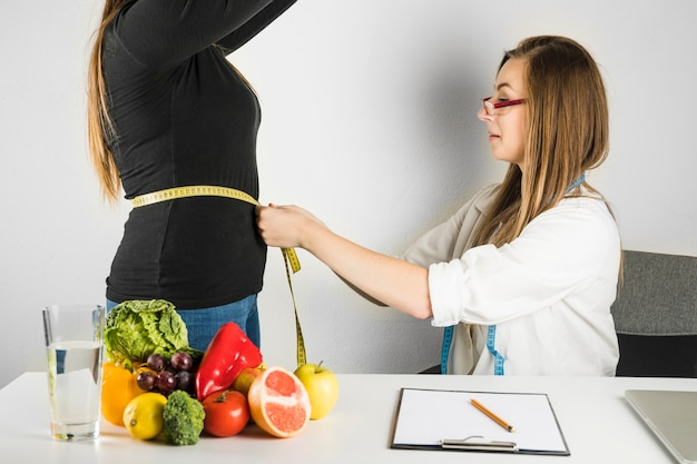 Female doctor measuring waist of woman in clinic Free Photo
