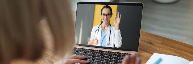 Женщина-врач на экране ноутбука, махнув рукой больному пациенту Premium Фотографии
