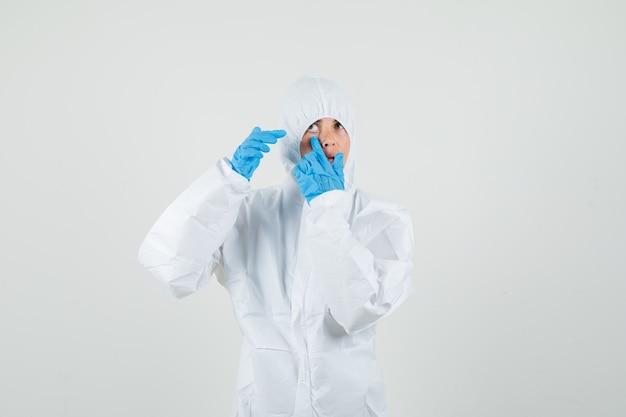 Medico femminile che indica alla sua palpebra tirata dal dito in tuta protettiva Foto Gratuite