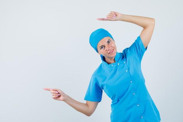 青い制服を着て横を指さし、陽気に見える女医。正面図。 無料写真