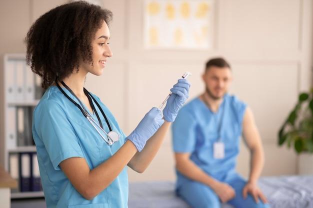 同僚のために予防接種を準備している女性医師 無料写真