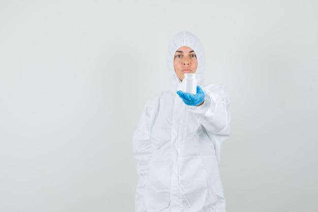 Medico femminile che mostra una bottiglia di pillole in tuta protettiva, guanti e aspetto serio Foto Gratuite