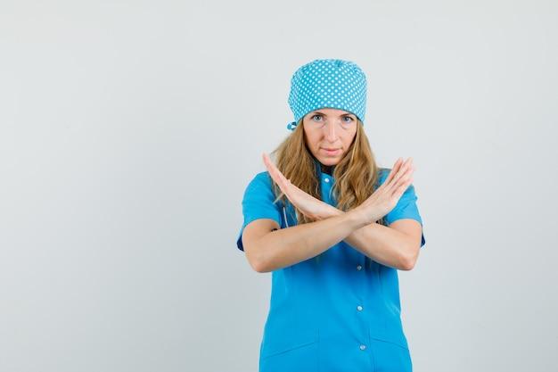 Женщина-врач показывает жест отказа в синей форме и выглядит серьезно Бесплатные Фотографии