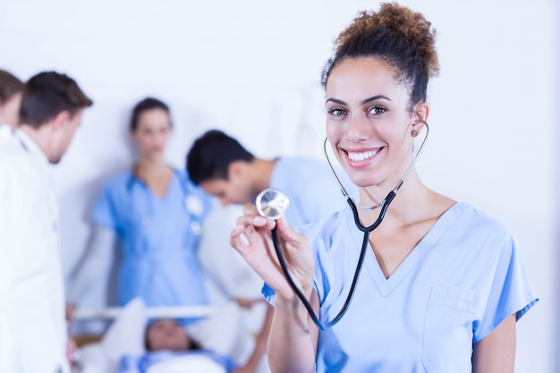 Female doctor showing stethoscope towards camera and other doctor examining a patient behind in hospital Premium Photo