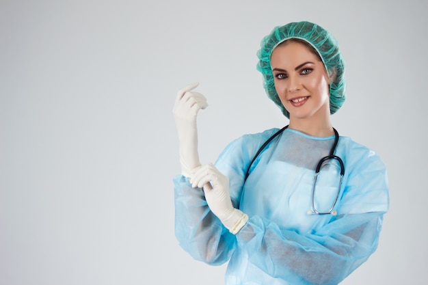 3d83151bd0b Female doctor surgeon in scrubs with medical hat putting on surgical  gloves. Premium Photo
