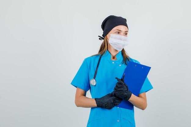 Dottoressa in uniforme, guanti, maschera che osserva da parte con appunti e penna Foto Gratuite