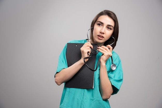 Female doctor using stethoscope on gray wall. Free Photo