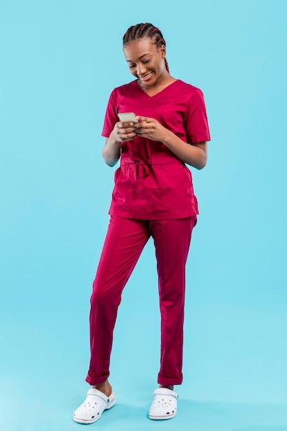 水色の壁の横にある電話を使用して女性の医者 無料写真