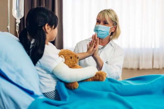 ほとんどの患者と話しているマスクを着ている女性医師 Premium写真