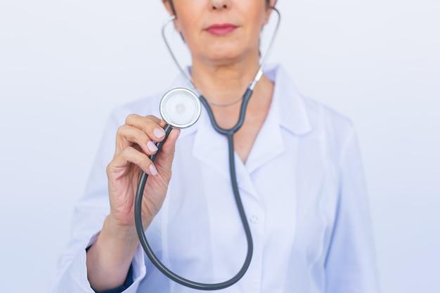 聴診器を持つ女性医師、白い壁を閉じる Premium写真