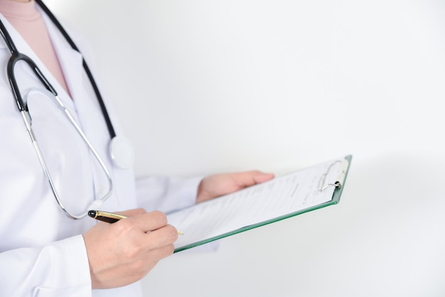 Female doctor with stethoscope holding a clipboard for medical records. Premium Photo