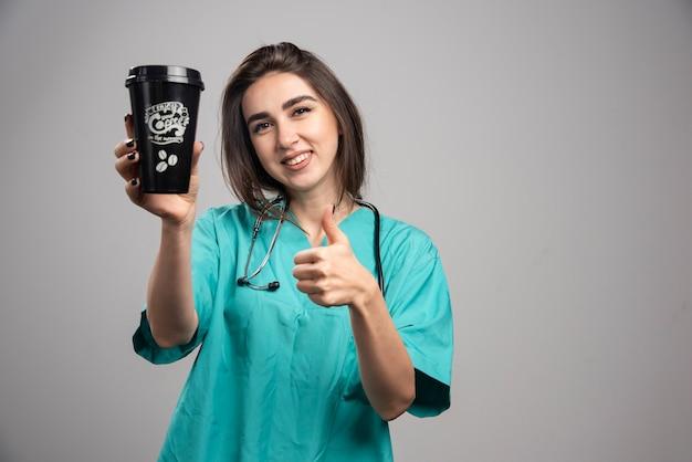 コーヒーを保持し、親指をあきらめる聴診器を持つ女性医師。 無料写真