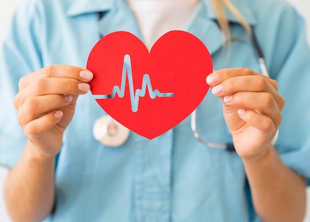 Женщина-врач со стетоскопом держит бумажное сердце с сердцебиением Premium Фотографии