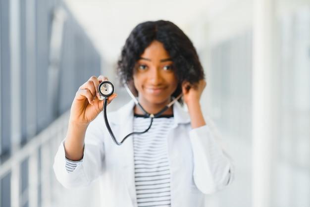 Женщина-врач со стетоскопом в коридоре больницы, держащем буфер обмена с операционной на заднем плане, здравоохранение и медицинская концепция, выборочный фокус. Premium Фотографии