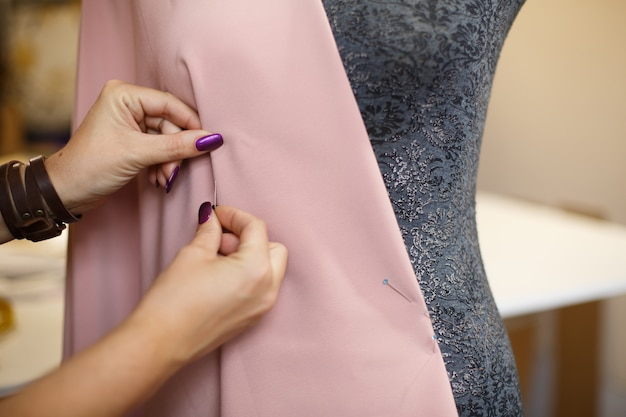 Female dressmaker attach fabric to mannequin with needles. creating dress design. tailor industry Premium Photo