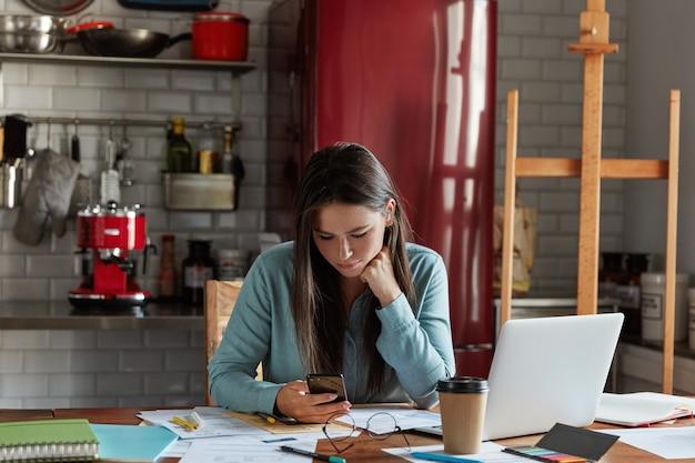 Dipendente di sesso femminile con capelli lunghi scuri, vestito con una camicia elegante, utilizza il telefono cellulare, lavora sul rapporto d'affari, beve caffè da asporto, utilizza il computer portatile, Foto Gratuite