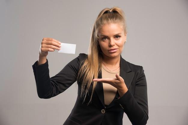 Impiegato femminile in vestito nero che presenta il suo biglietto da visita. Foto Gratuite