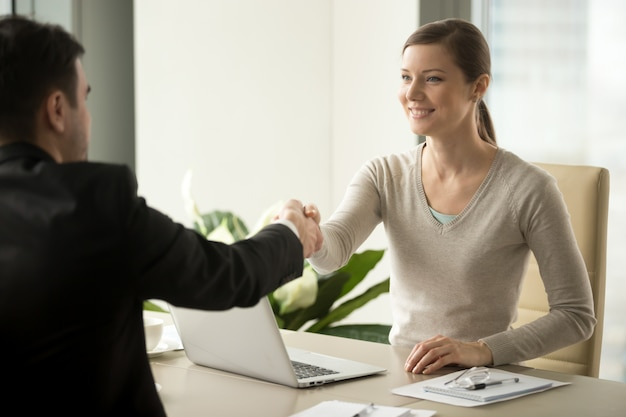 Female employee handshaking with male client Free Photo
