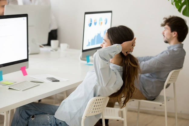 Female employee relaxing from computer work holding hands behind head Free Photo