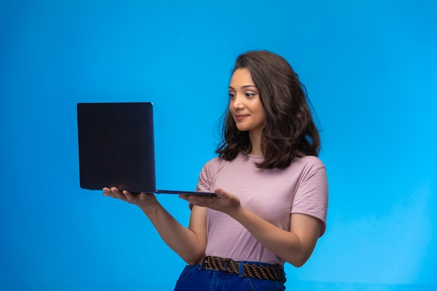 Female employee with a black laptop having video call and smiling. Free Photo