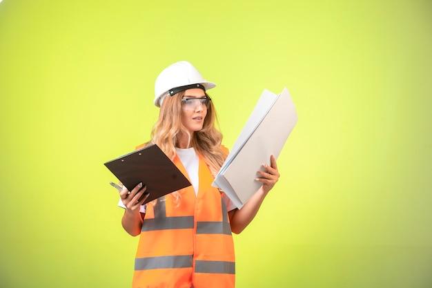 Ingegnere femminile in casco e attrezzi che tengono il piano di progetto e l'elenco dei rapporti. Foto Gratuite
