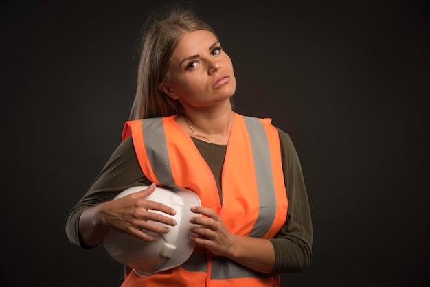 Ingegnere femminile che tiene un casco bianco e gli attrezzi da portare. Foto Gratuite