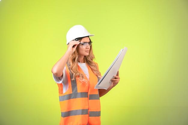 プロジェクト計画を保持し、眼鏡をかけているヘルメットとギアの女性エンジニア。 無料写真