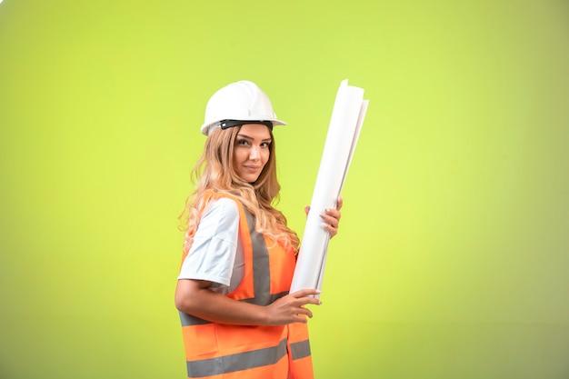 建設計画を保持し、自信を持って見えるヘルメットとギアの女性エンジニア。 無料写真