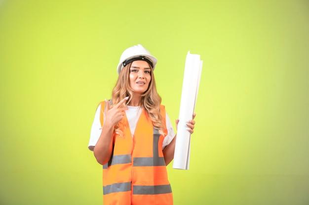 헬멧 및 장비 건설 계획을 잡고 그것을 가리키는 여성 엔지니어. 무료 사진