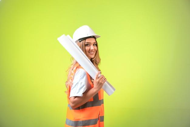 헬멧 및 장비 건설 계획을 잡고 웃 고있는 여성 엔지니어. 무료 사진