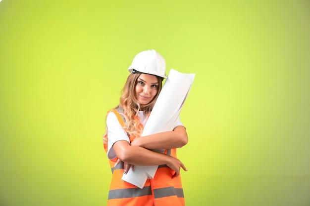 헬멧 및 장비 건설 계획을 잡고 여성 엔지니어. 무료 사진