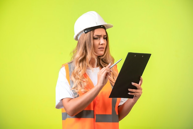 レポートをチェックする白いヘルメットとギアの女性エンジニア。 無料写真