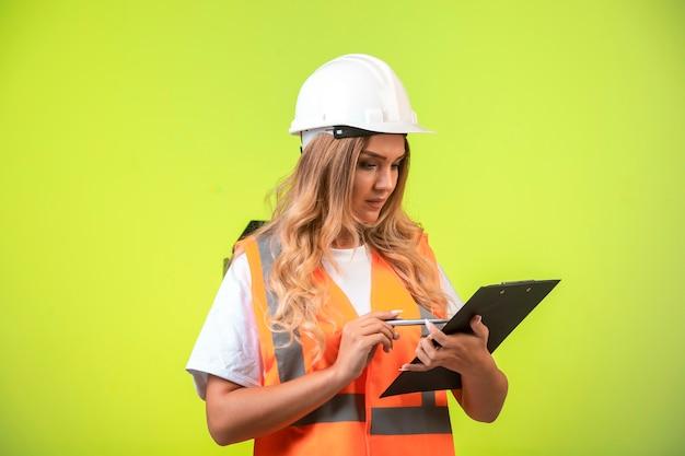 흰색 헬멧 및 장비 체크리스트를 들고 보고서를 찾고있는 여성 엔지니어. 무료 사진