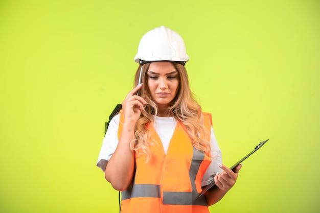 チェックリストを保持し、覚えようとしている白いヘルメットとギアの女性エンジニア。 無料写真