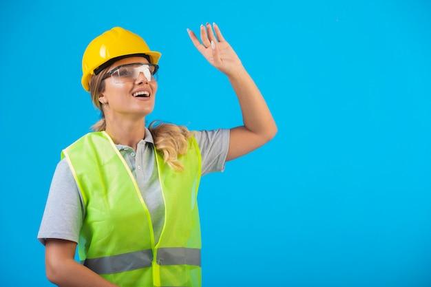 予防眼鏡をかけ、見上げる黄色いヘルメットとギアの女性エンジニア。 無料写真