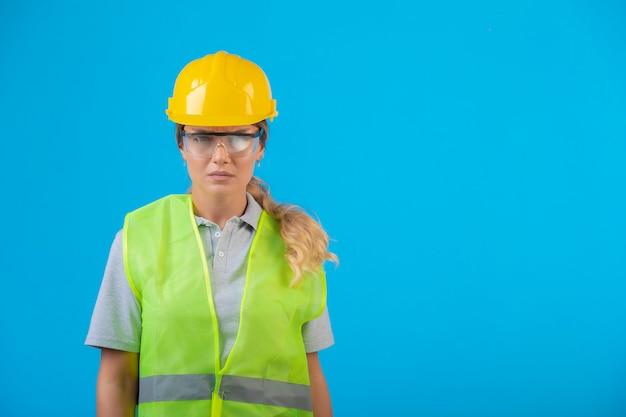 노란색 헬멧 및 예방 안경을 착용하는 장비에 여성 엔지니어. 무료 사진