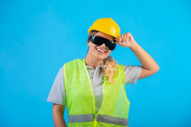 노란색 헬멧과 장비를 착용하고 광선 예방 안경을 착용하고 긍정적 인 느낌을주는 여성 엔지니어. 무료 사진