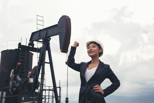 Female engineer standing with working oil pumps with a white sky . Free Photo