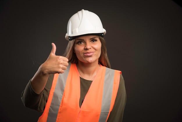 白いヘルメットとギアを身に着けて、親指を立てるサインをあきらめる女性エンジニア。 無料写真