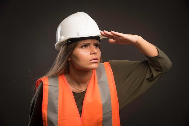 Ingegnere femminile che indossa un casco bianco e attrezzi e guarda avanti. Foto Gratuite