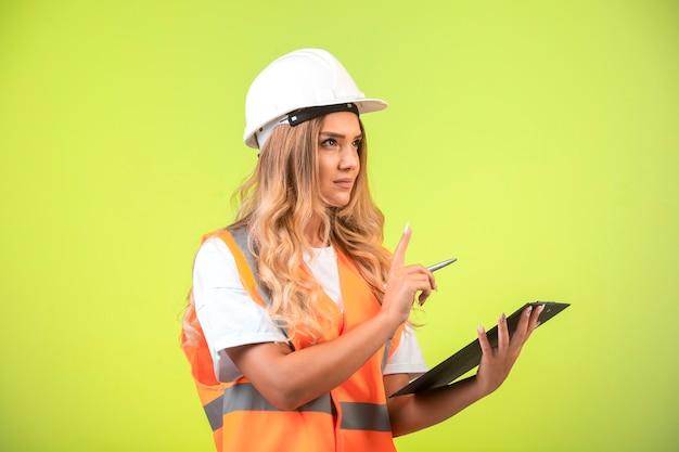Ingegnere femminile in casco bianco e attrezzi che tengono la lista di controllo e chiede il discorso. Foto Gratuite