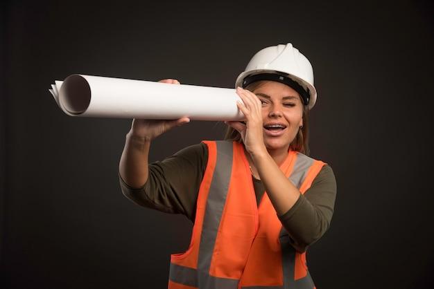 Ingegnere femminile con un casco bianco che tiene il piano di progetto e lo guarda. Foto Gratuite
