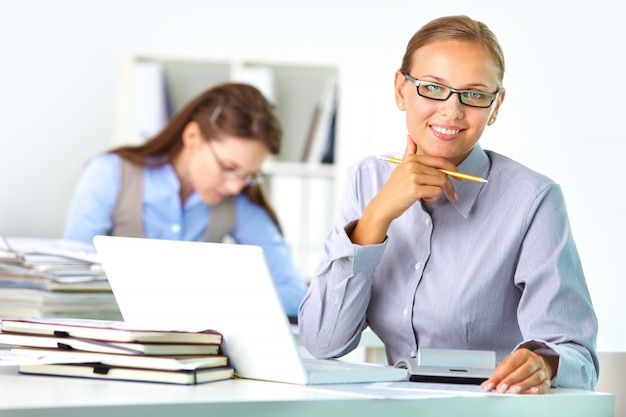 Female executive with glasses at her workplace Free Photo