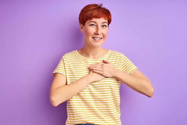 여성은 감사를 표현하고, 가슴에 손을 잡고, 친절을 느낍니다. 보라색 벽에 절연 프리미엄 사진